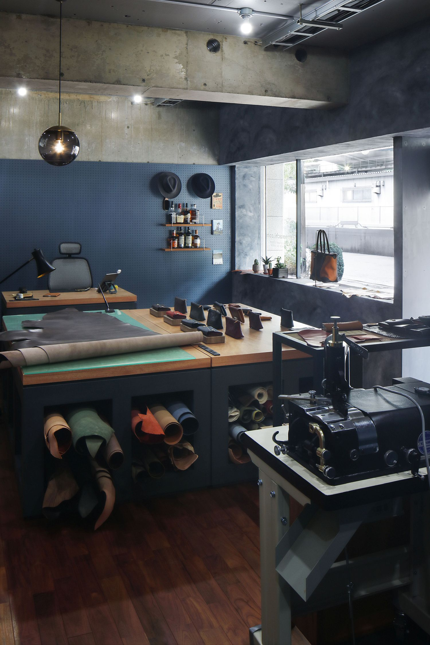 Interior of the leather shop combines modern blue finishes with wood and exposed concrete