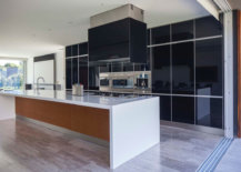 Kitchen-with-a-large-central-sialnd-black-polished-backdrop-and-stainless-steel-appliances-35144-217x155