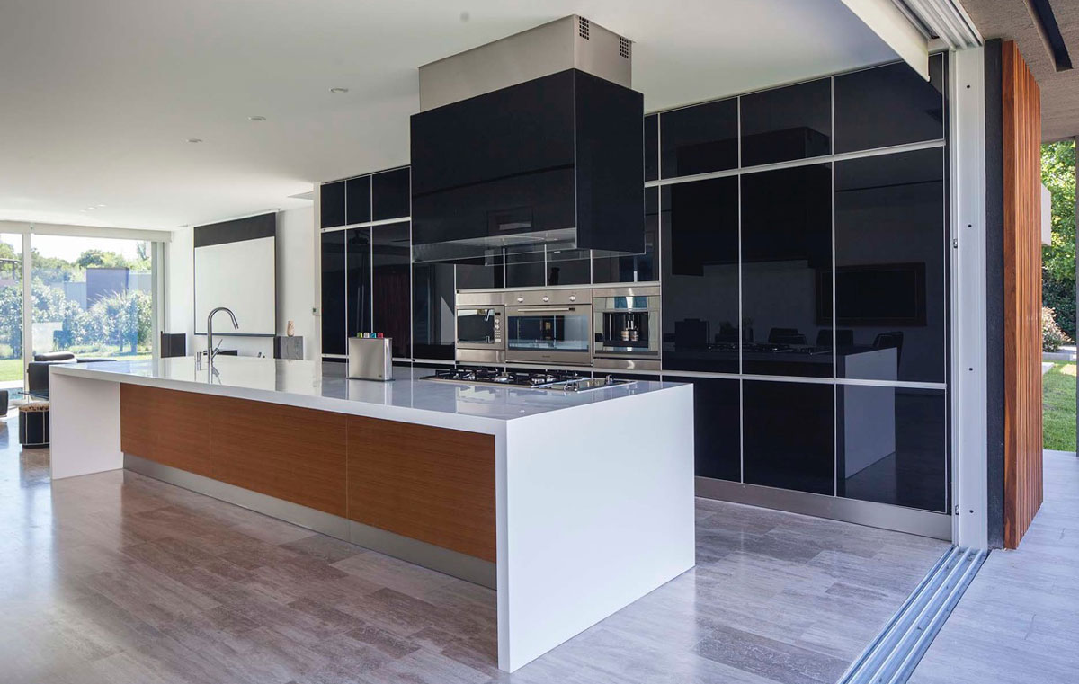 Kitchen-with-a-large-central-sialnd-black-polished-backdrop-and-stainless-steel-appliances-35144