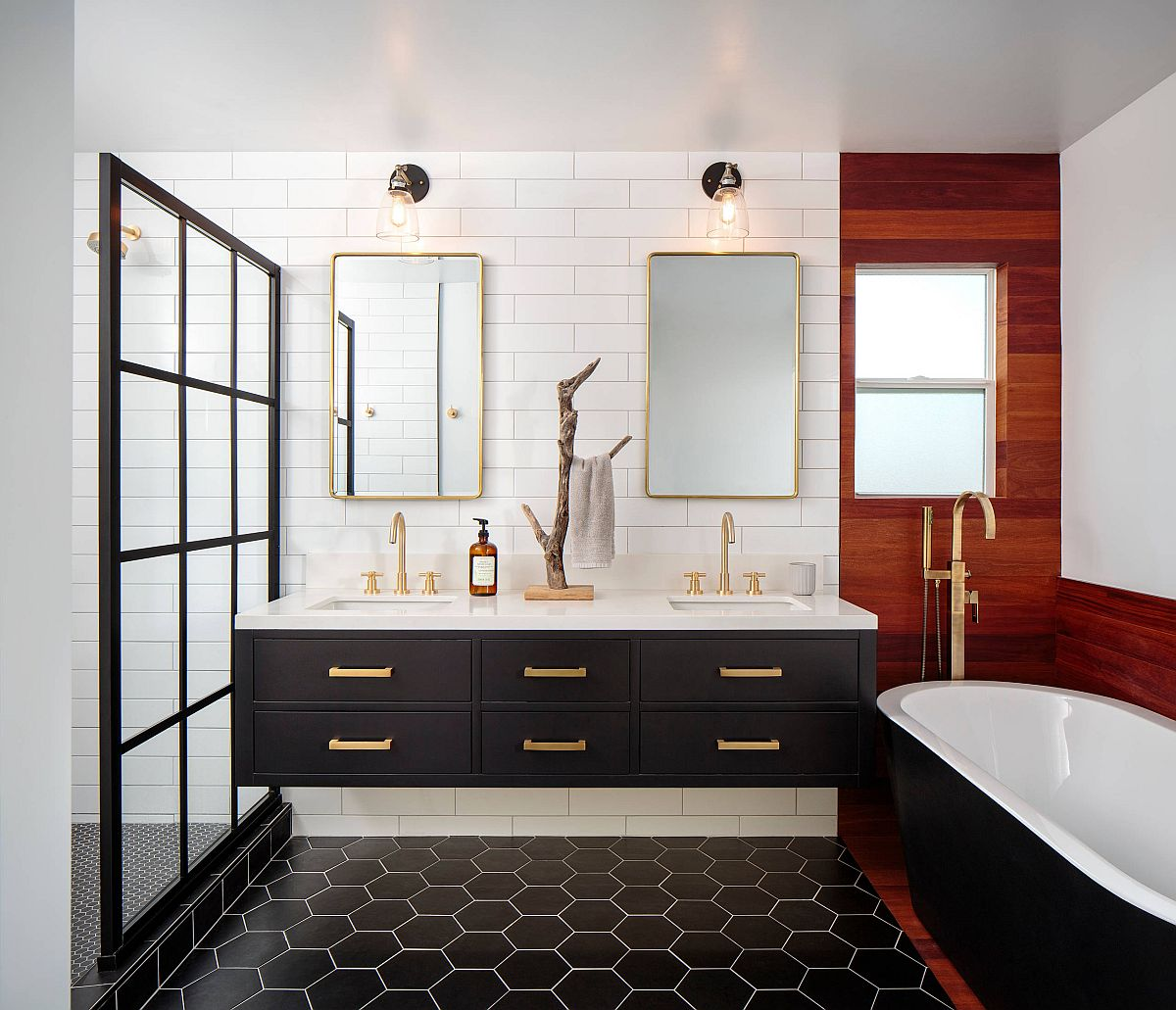 Master bathroom in black and white with brass handles and frames along with wooden accent section