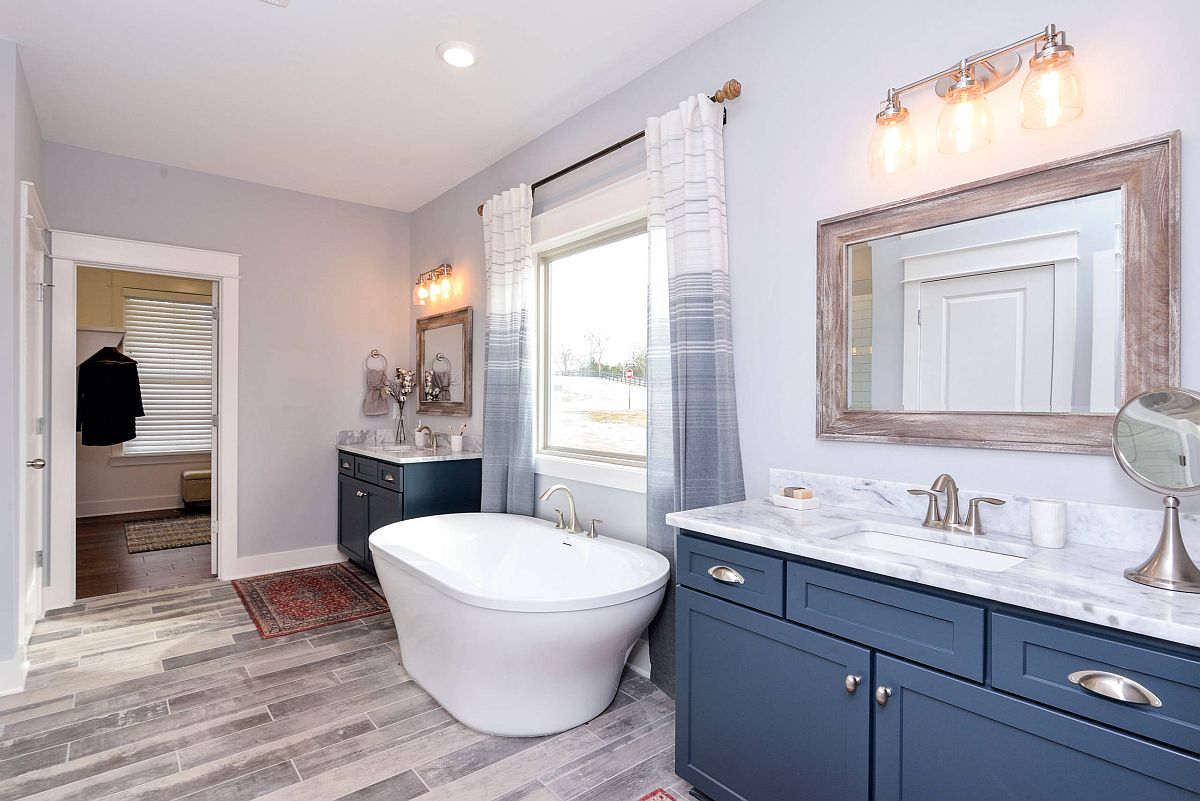 Master bathroom in gray with wooden floor and a bright blue vanity
