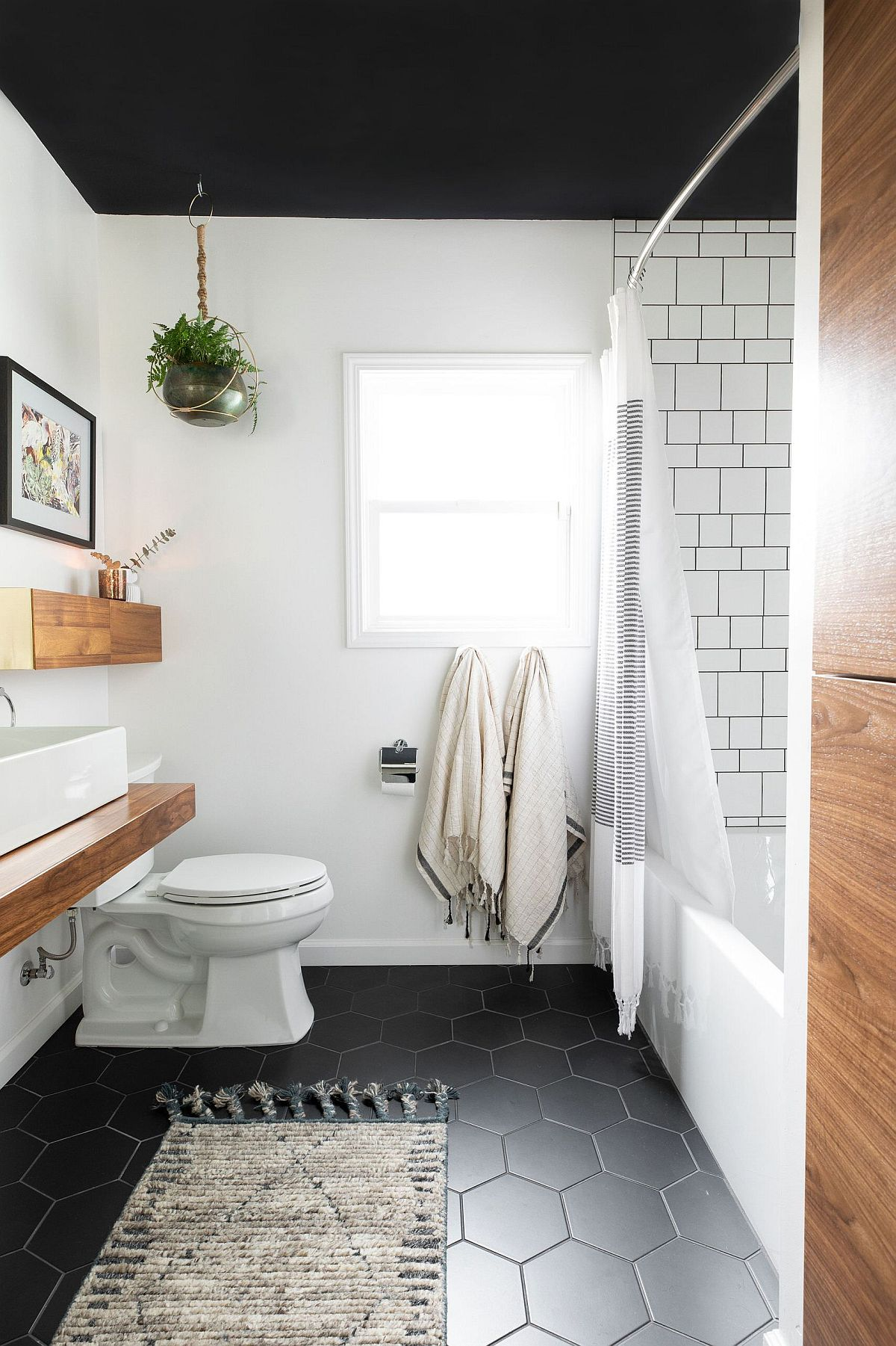 Modern bathroom in black and white with wooden accents and vanity has a floor with hexagonal tiles
