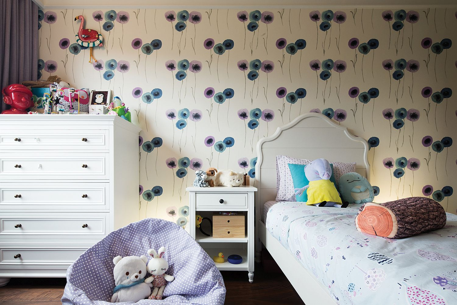 Modern girl's bedroom idea with wallpapered backdrop and smart decor