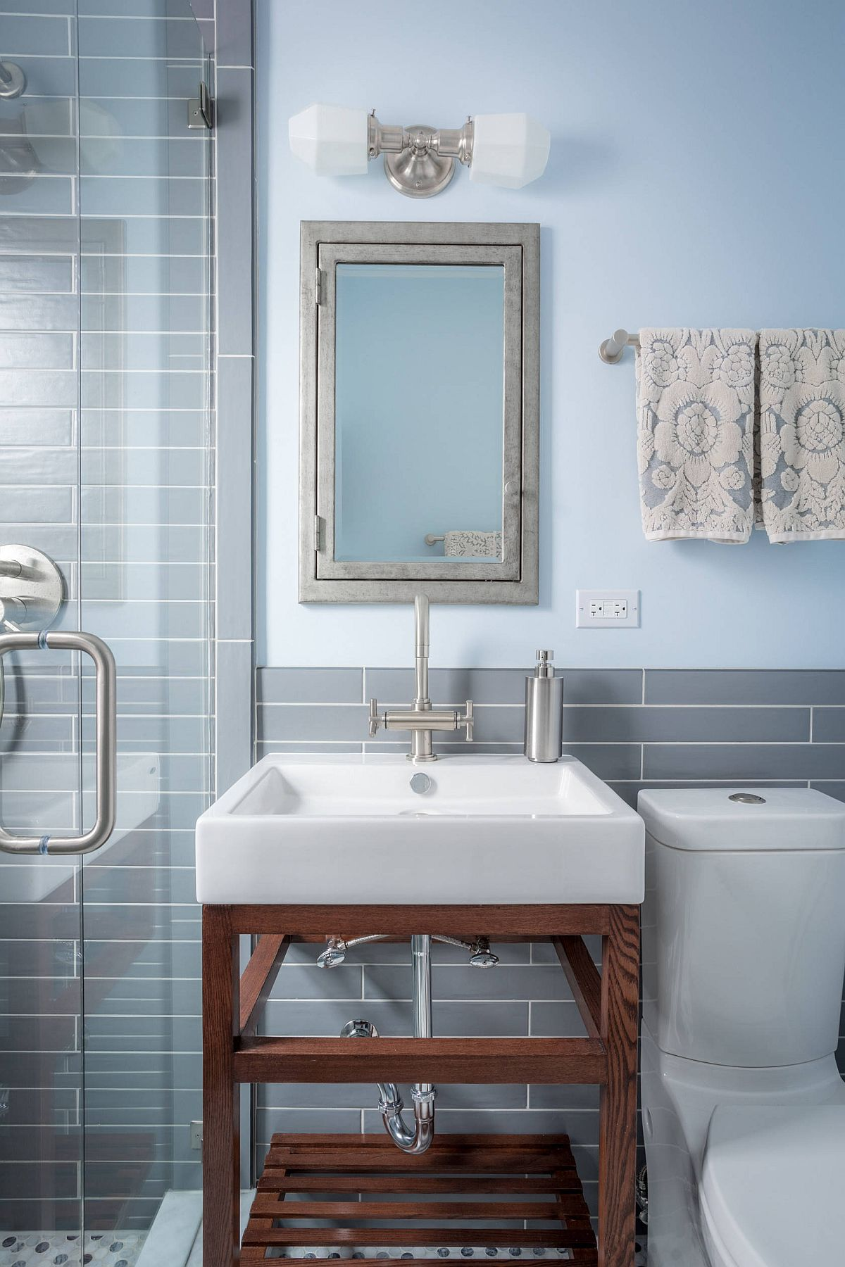 Modern gray and blue bathroom with small wooden vanity and lovely lighting