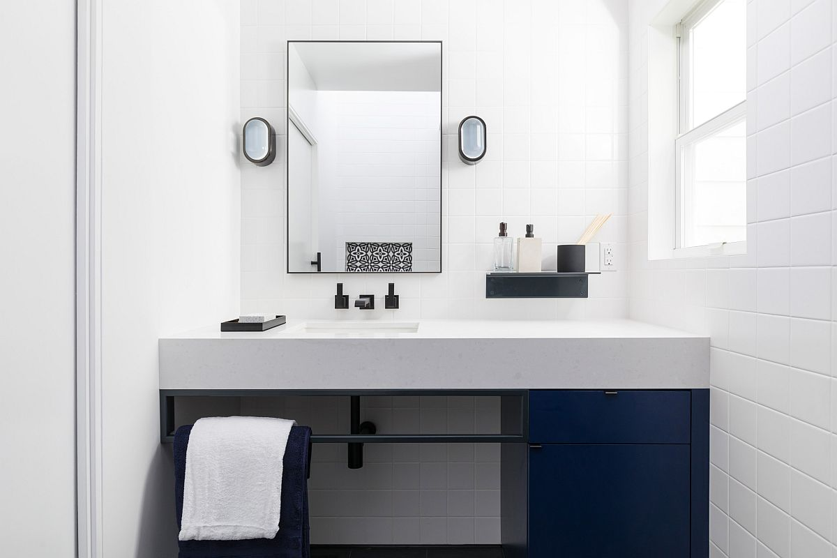 Monochromatic bathroom in white with deep blue cabinets and contemporary style