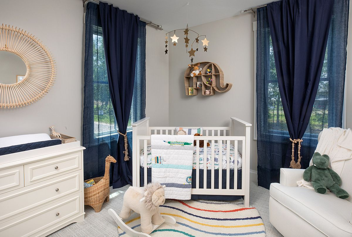 Navy blue curtains, bedding and accessories accentuate the beach style of this nursery