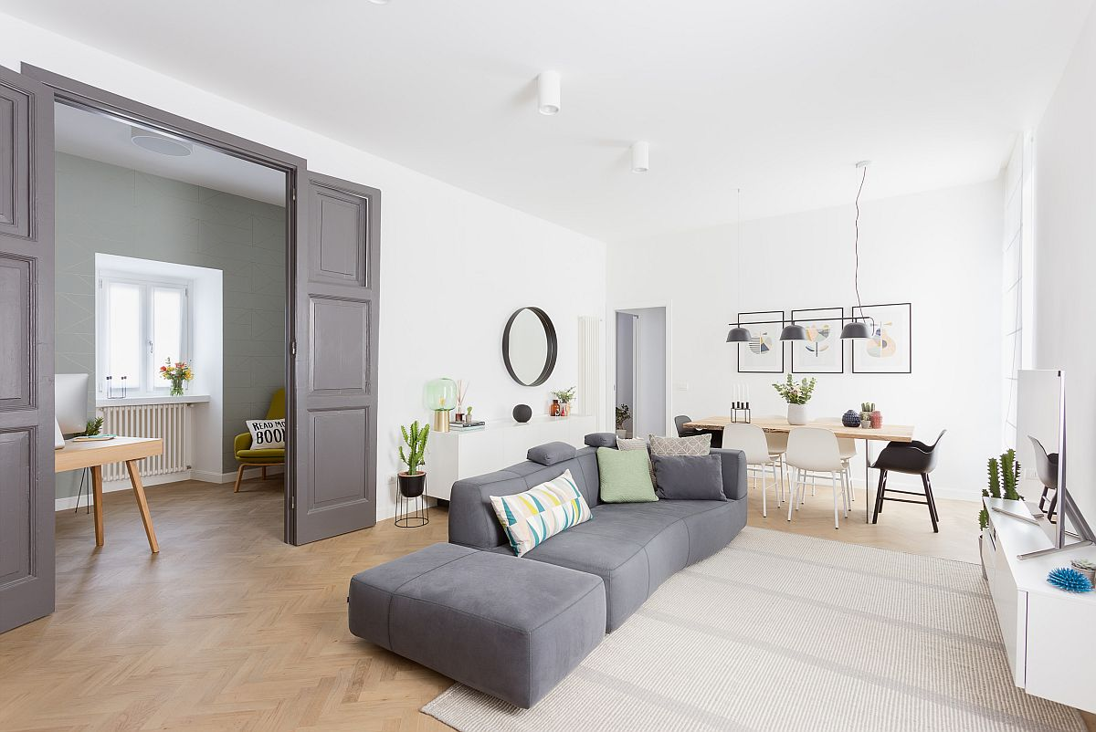 Open plan living area in white with Scandinavian style and large gray couch