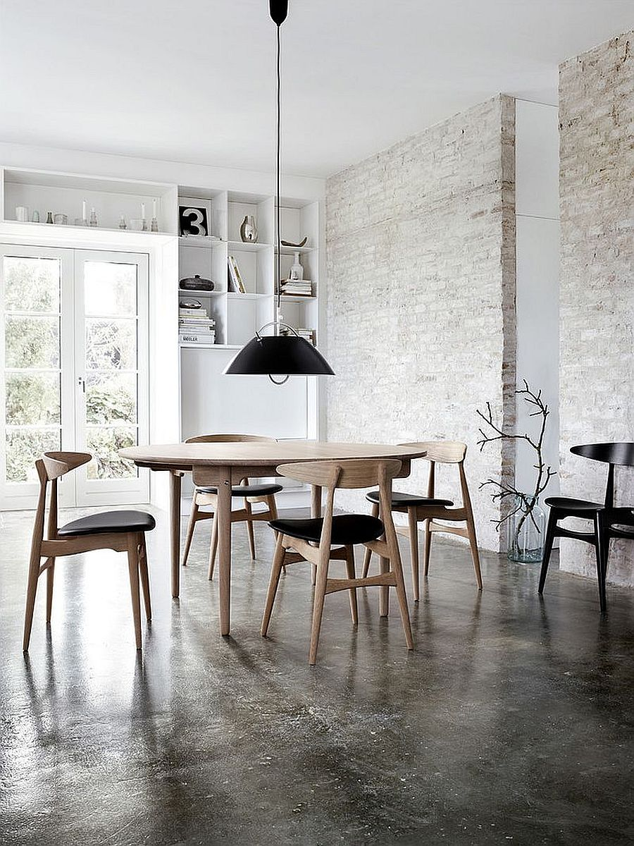 Painting the exposed brick wall white in the industrial style dining rooms with black chairs