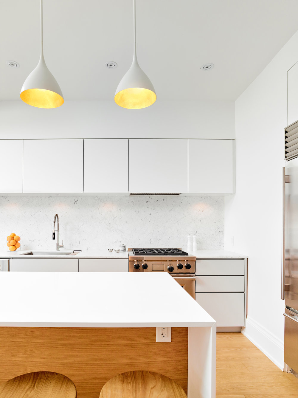 Pendants accentuate the modern minimal style of the kitchen while adding metallic sparkle