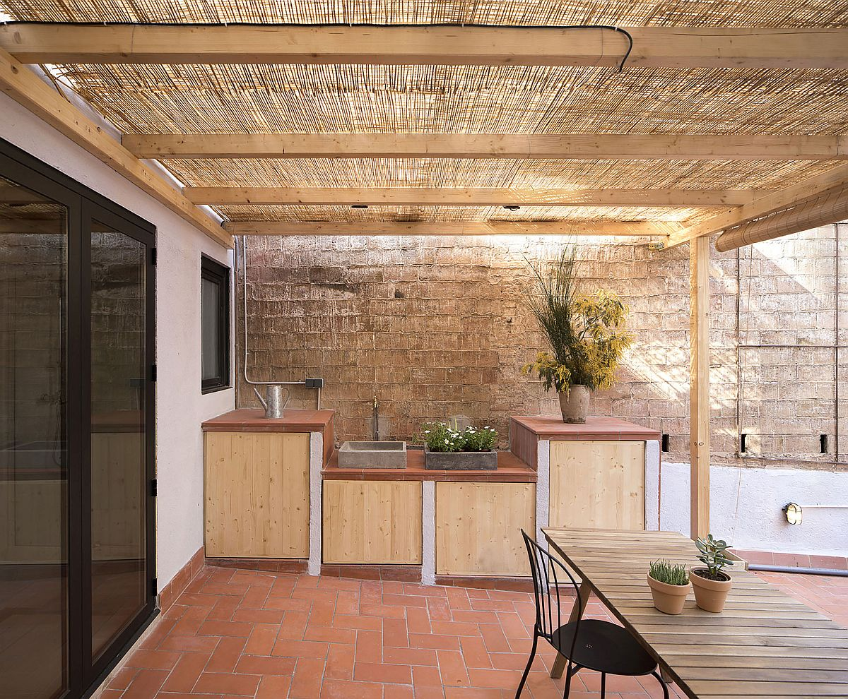 Pergola structure offers shade to the apartment even while extending the living area