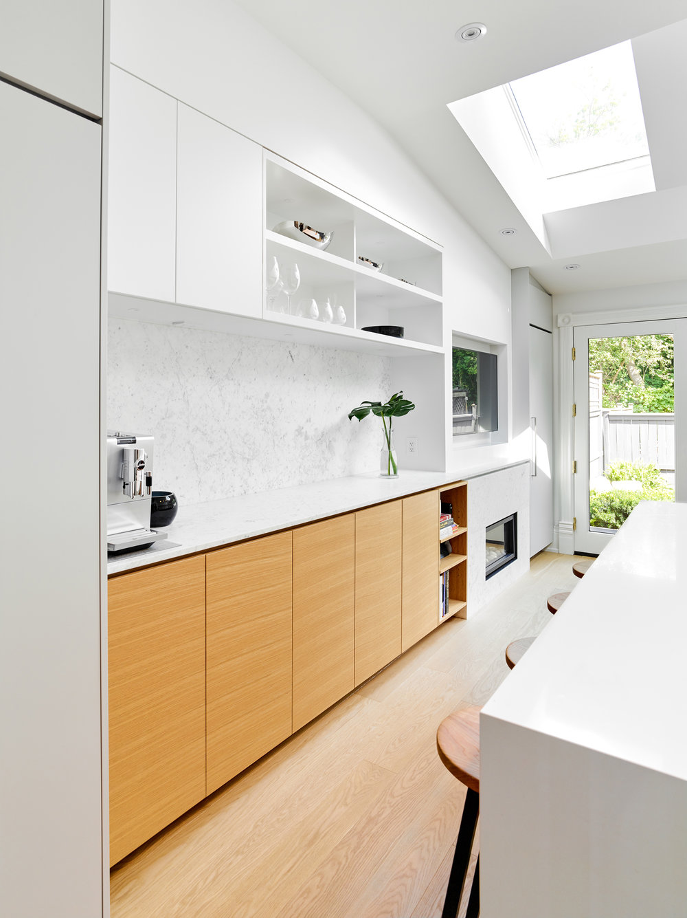 Relaxing social kitchen in white with polished finishes and connectivity with the outdoors