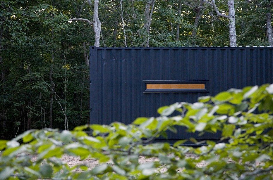 Reused shipping containers painted black to create modern New York art studio
