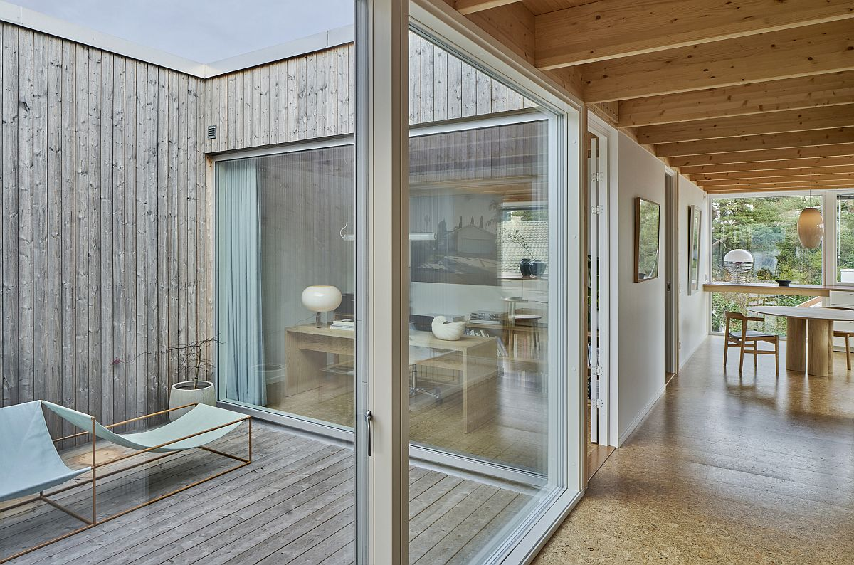 Simple and elegant atrium in wood with Scandinavian style and sliding glass doors