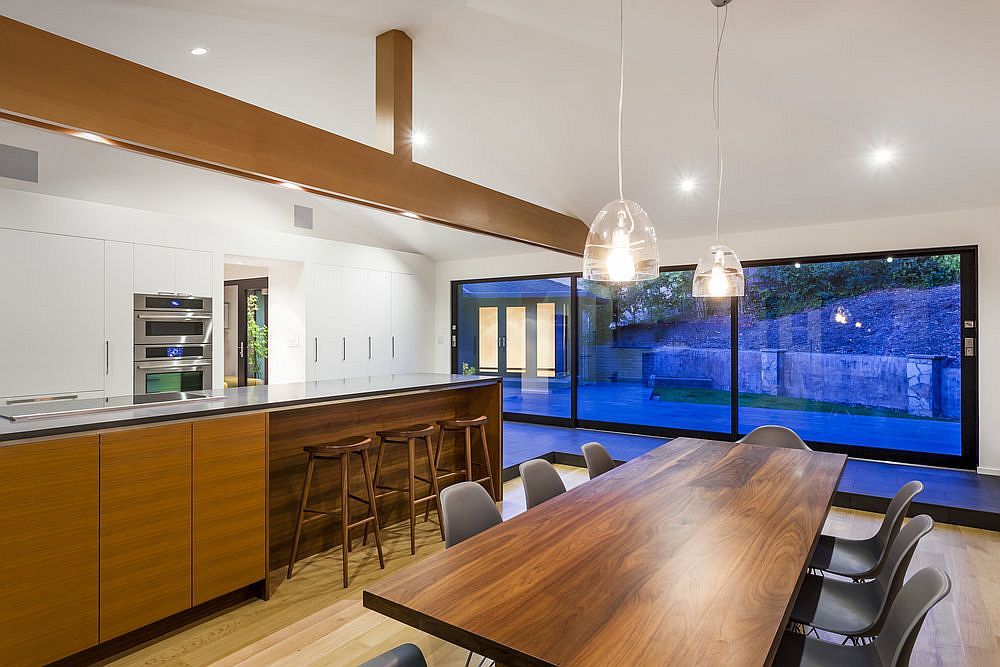 Sliding glass doors connect the dining and kitchen with the yard outside