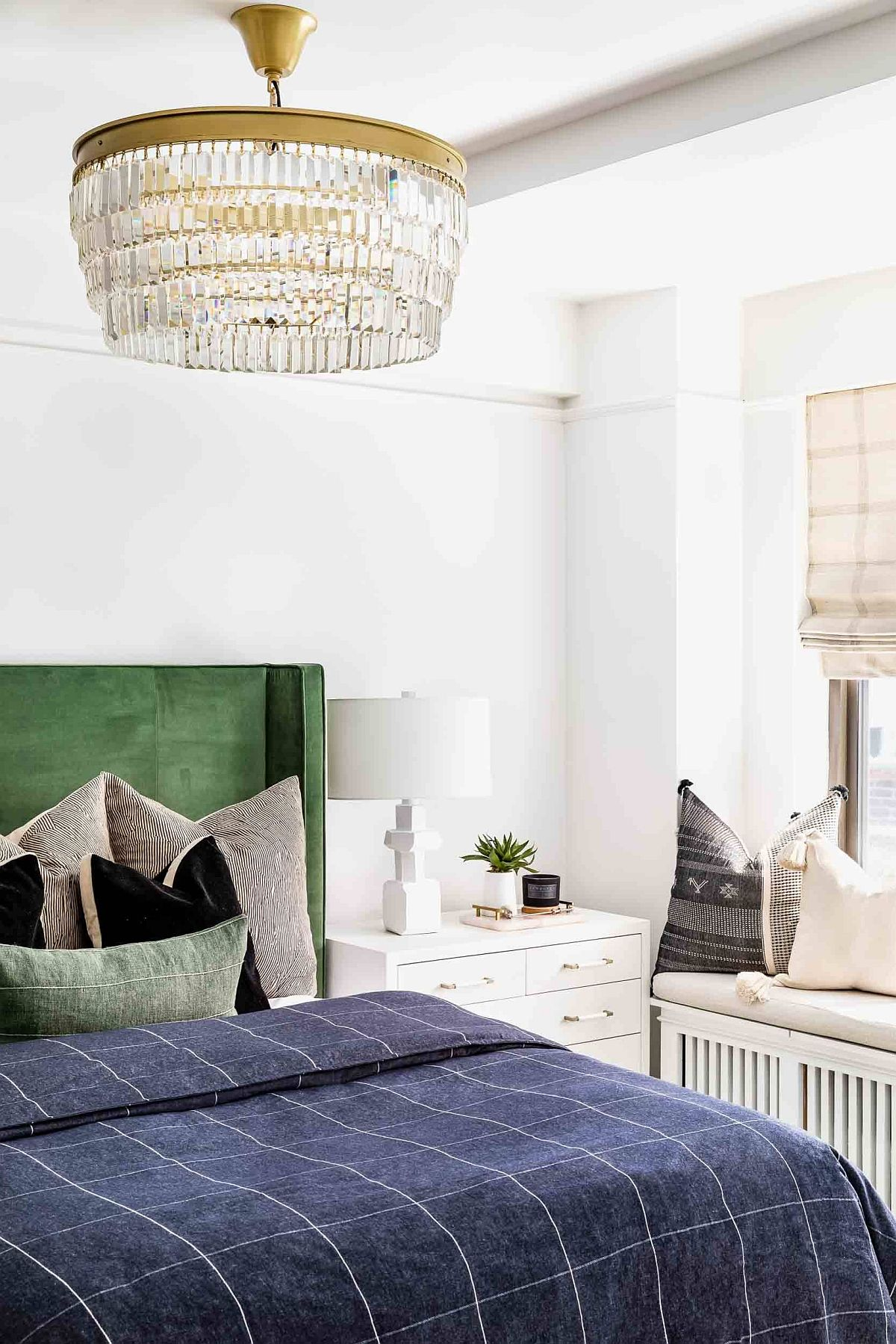 Small-and-space-savvy-bedroom-of-NYC-apartment-with-green-headboard-and-window-seat-55744