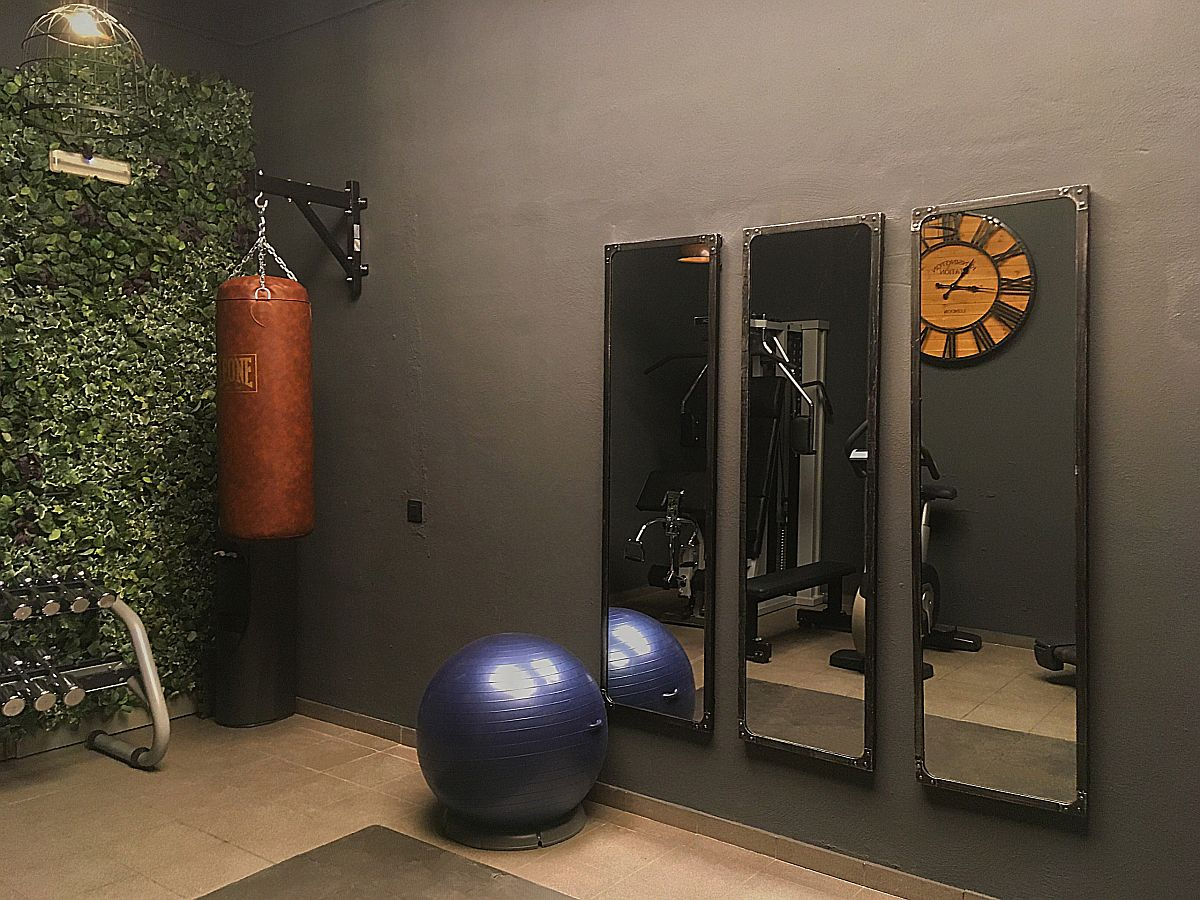 Small-basement-home-gym-in-Barcelona-with-mirrors-and-a-green-wall-53317