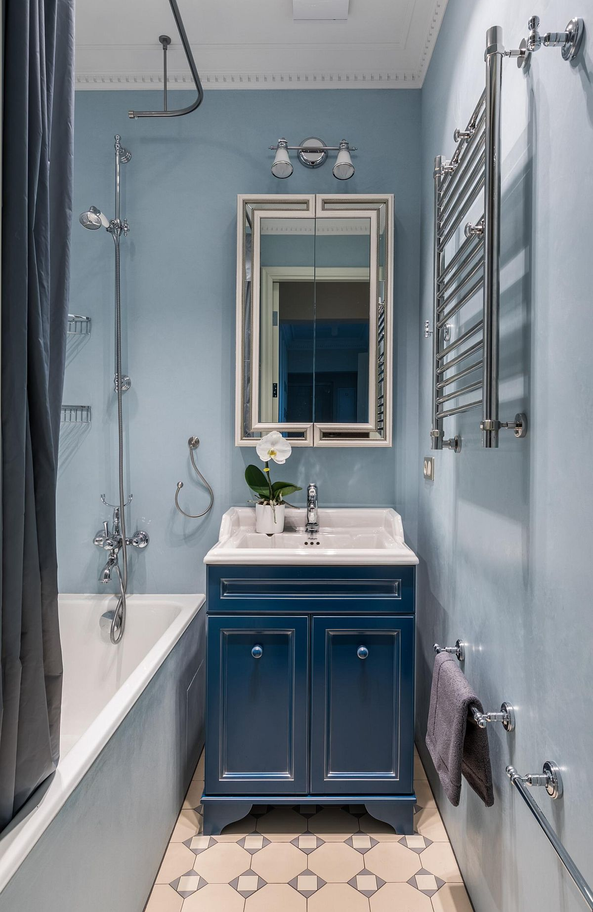 Small bathroom in light blue and white of Moscow home with a dark blue vanity and space-savvy design