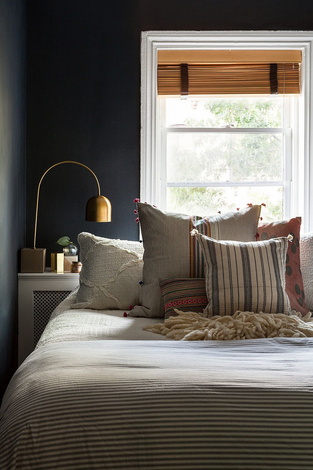 Small bedroom with dark gray backdrop, large window and unmistakable New York charm