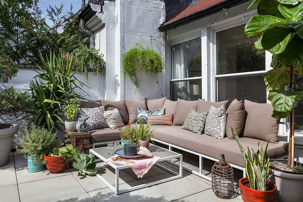 Small patio with large outdoor sectional, coffee table and a whole lot of greenery all around