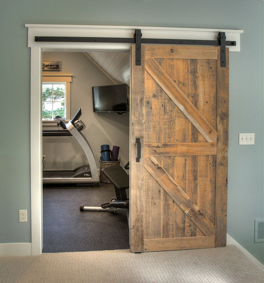 Small-transitional-style-home-gym-sits-behind-the-sliding-arn-door-in-here-49859