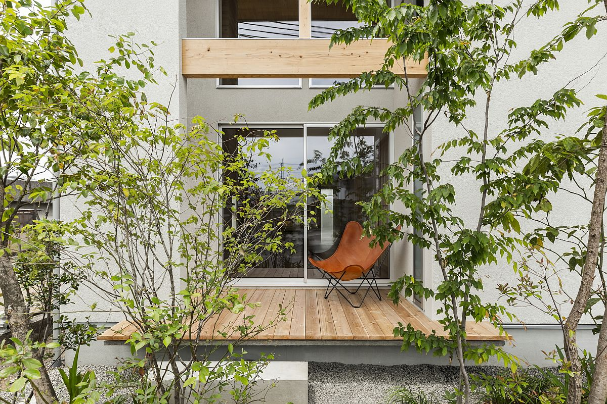 Small wooden deck of the house surrounded by greenery provides a relaxing refuge