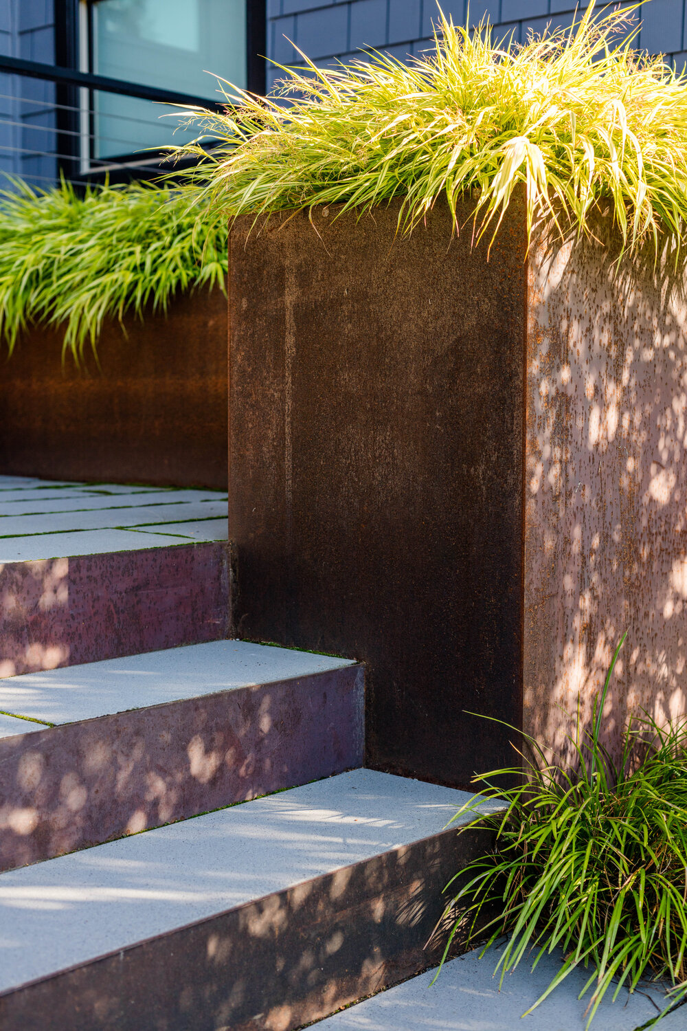 Steel and concrete steps welcome you inoto the lovely home and series of patios around it