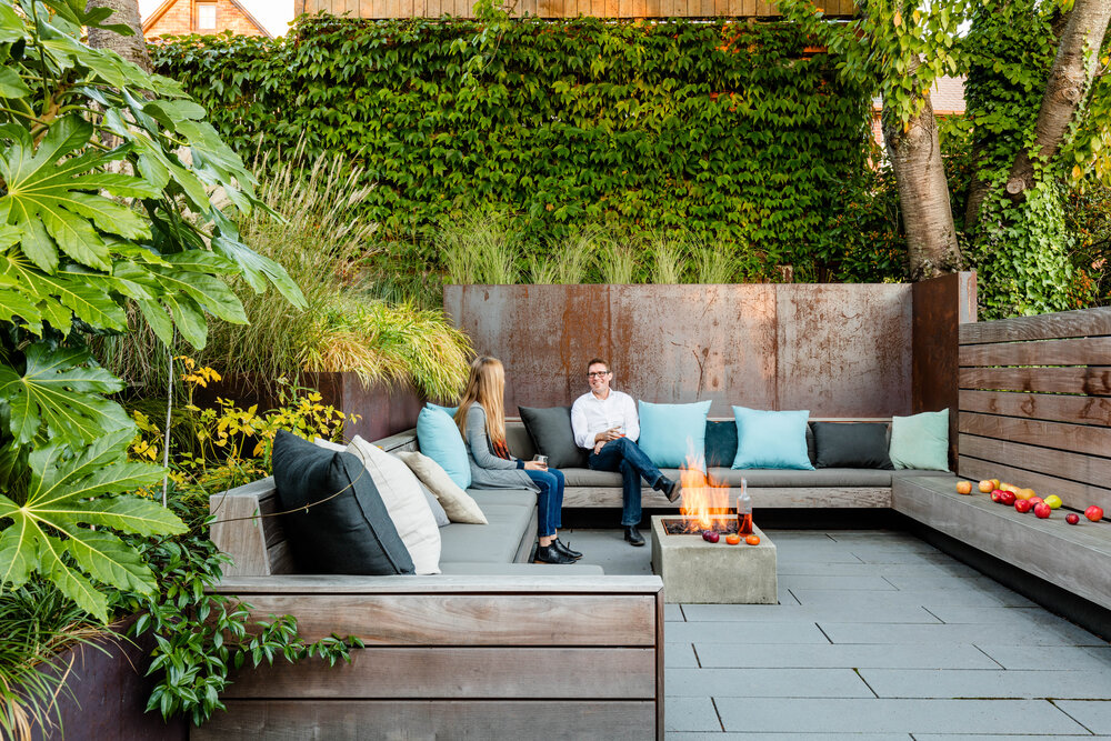 Sunken patio becomes private outdoor conversation pit with a gorgeous fireplace and comfy seating