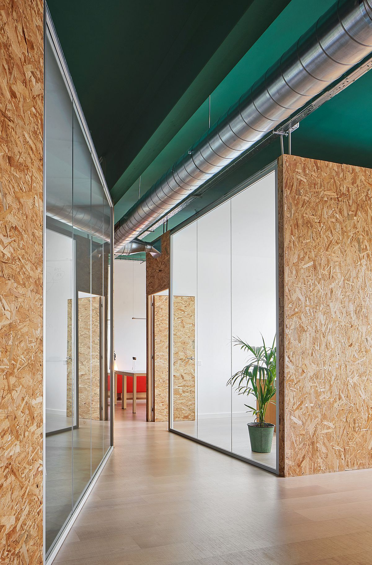 Two distinct boxes inside the office building serve as meeting room and management space