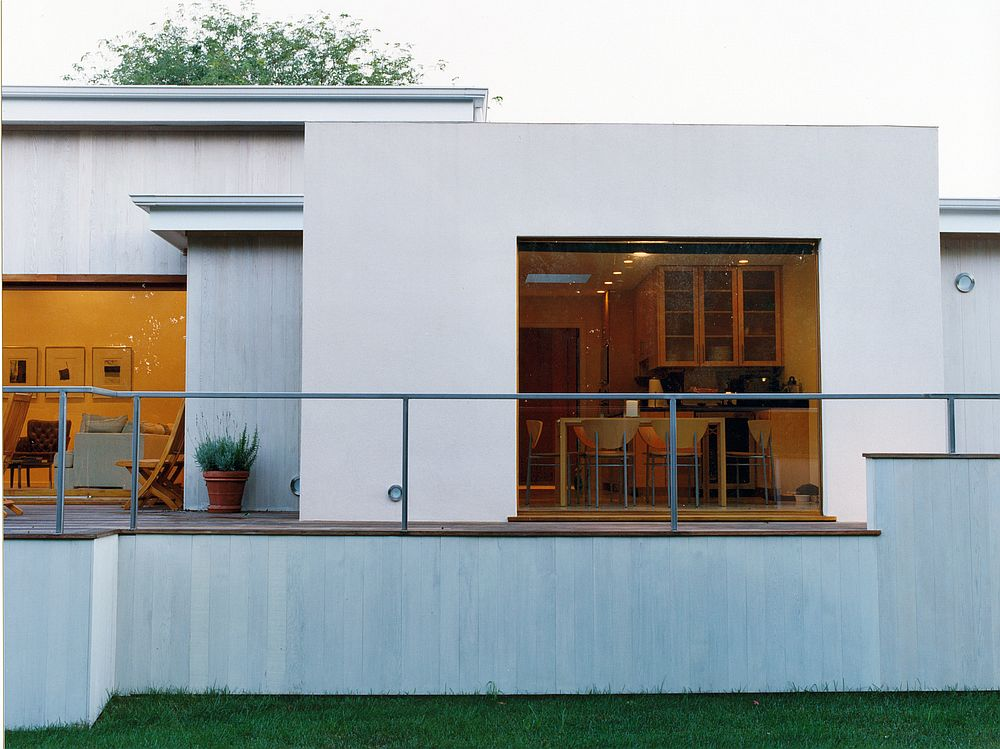 White extension of the ranch with glass walls connecting it to the exterior