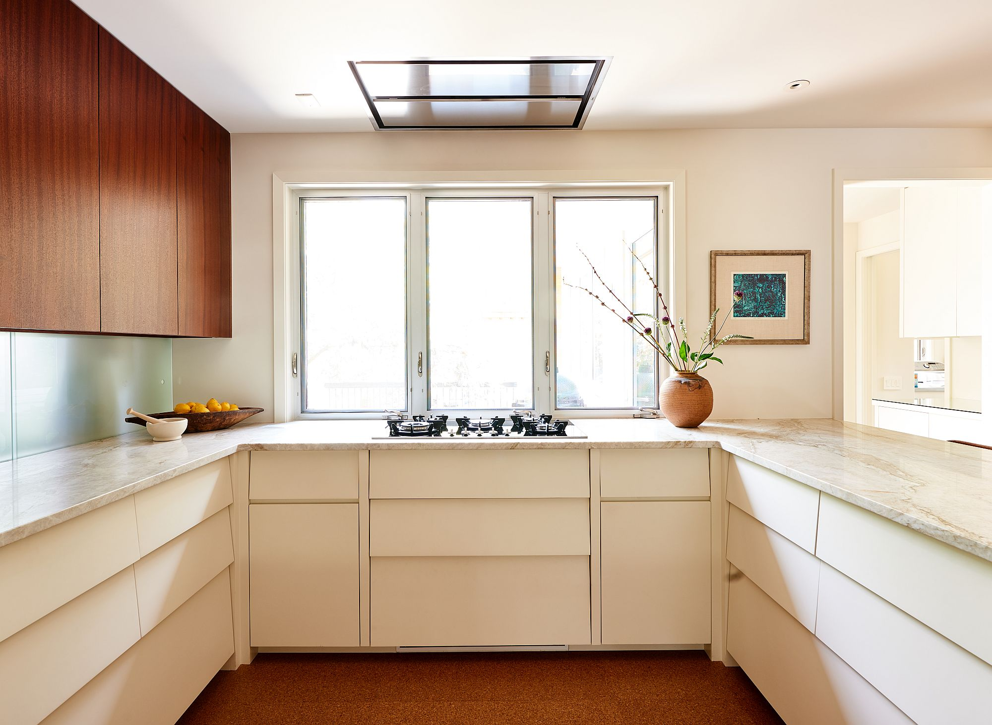 Windows bring natural light into the spacious kitchen with cork floors