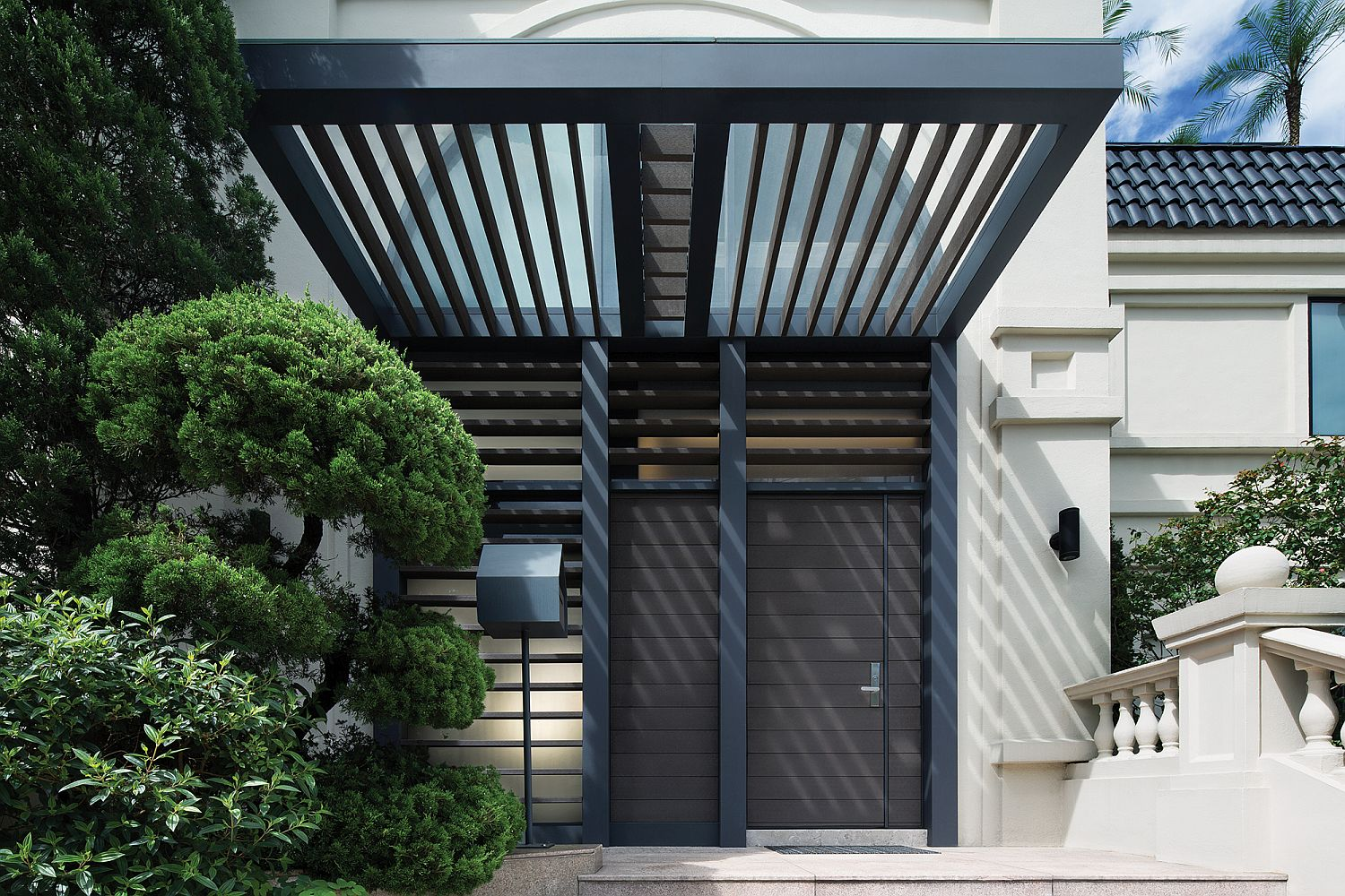 Wood and metal canopy for the front entrance offers shade and creates an interesting facade