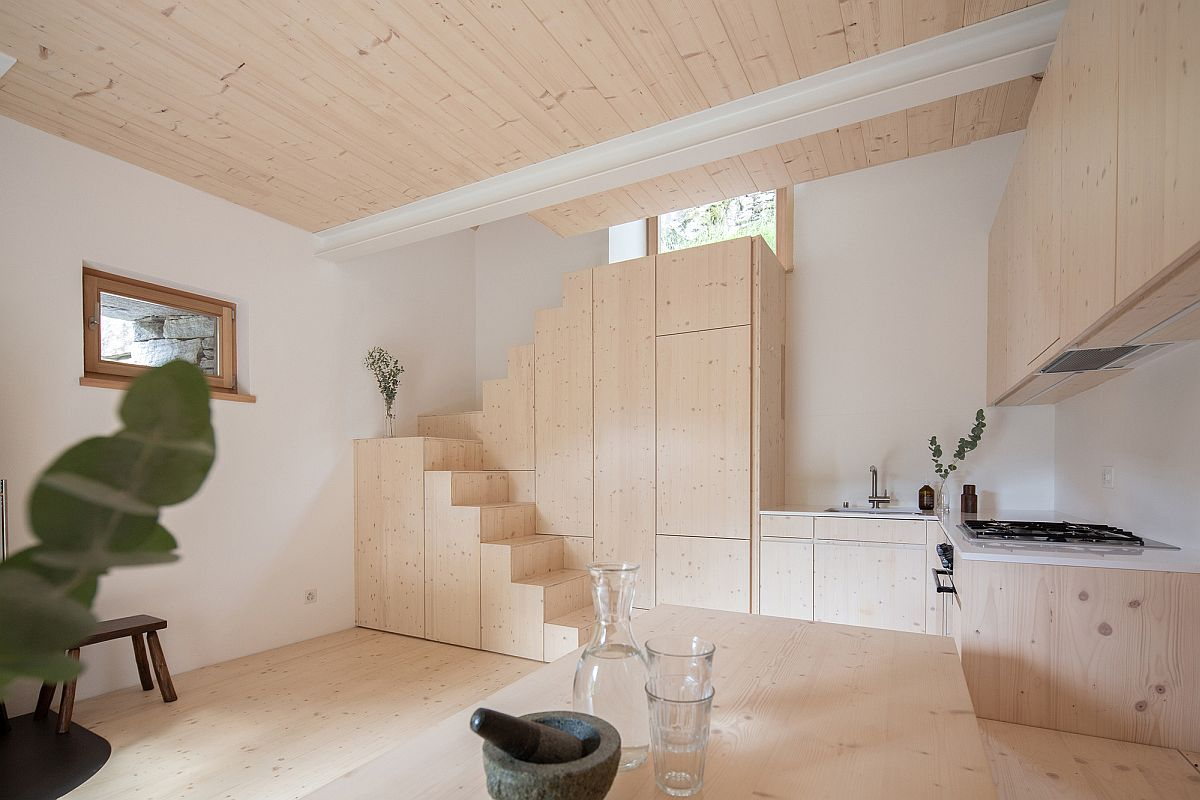 Wood and white living area of the converted barn is filled with natural light