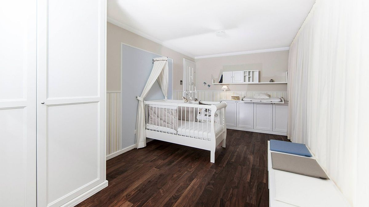 A bit of biege adds to the elegance of this farmhouse nursery in white with wood floor and ample space
