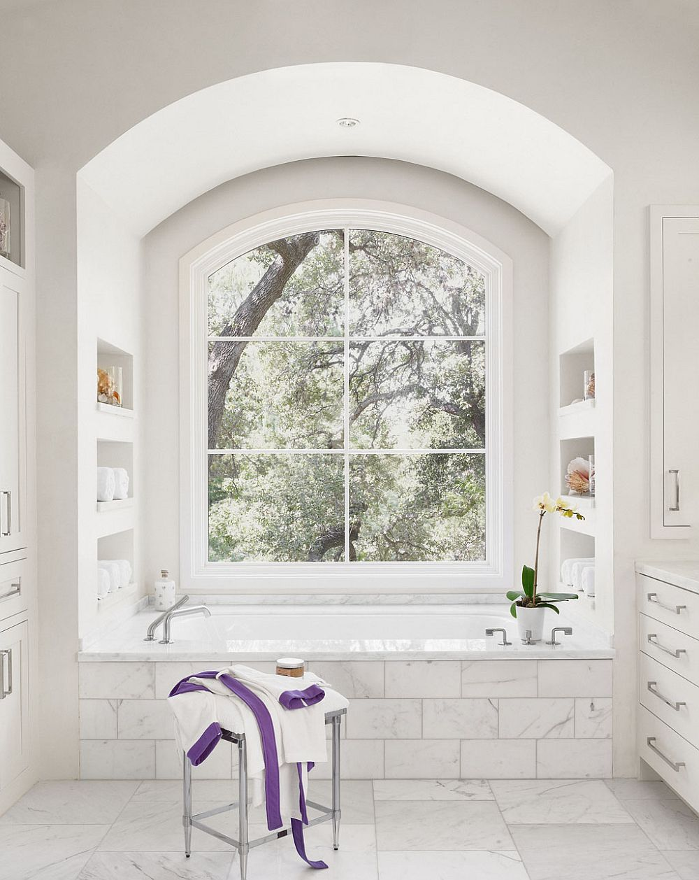 All white modern bathroom of the Texas home with a view of the leafy outdoors
