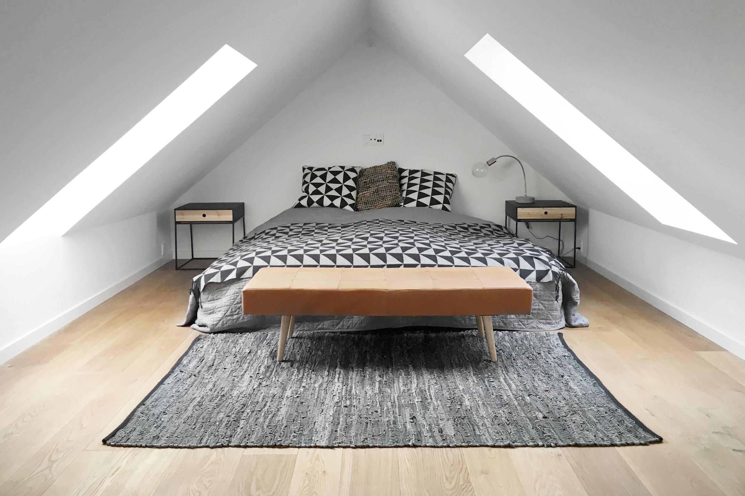 Attic bedroom with ample natural light and bedding that adds pattern