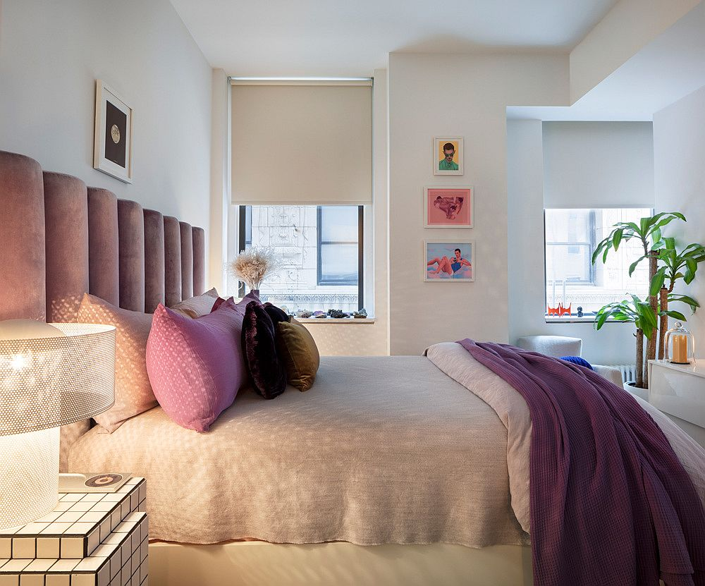 Bedding headboard and wall art pieces bring both color and contrast to the small bedroom in white