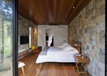 Bedroom-of-the-retreat-with-stone-walls-sliding-glass-doors-and-wooden-flooring-17053-217x155