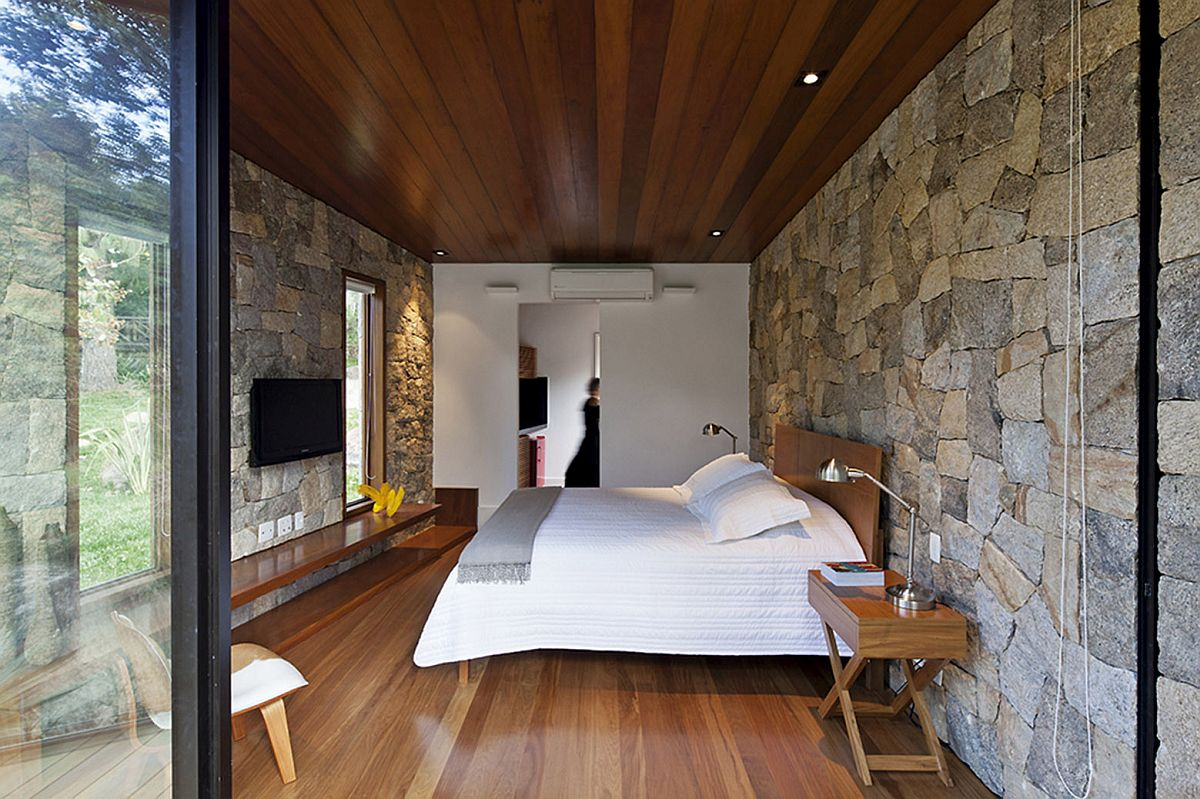 Bedroom of the retreat with stone walls, sliding glass doors and wooden flooring