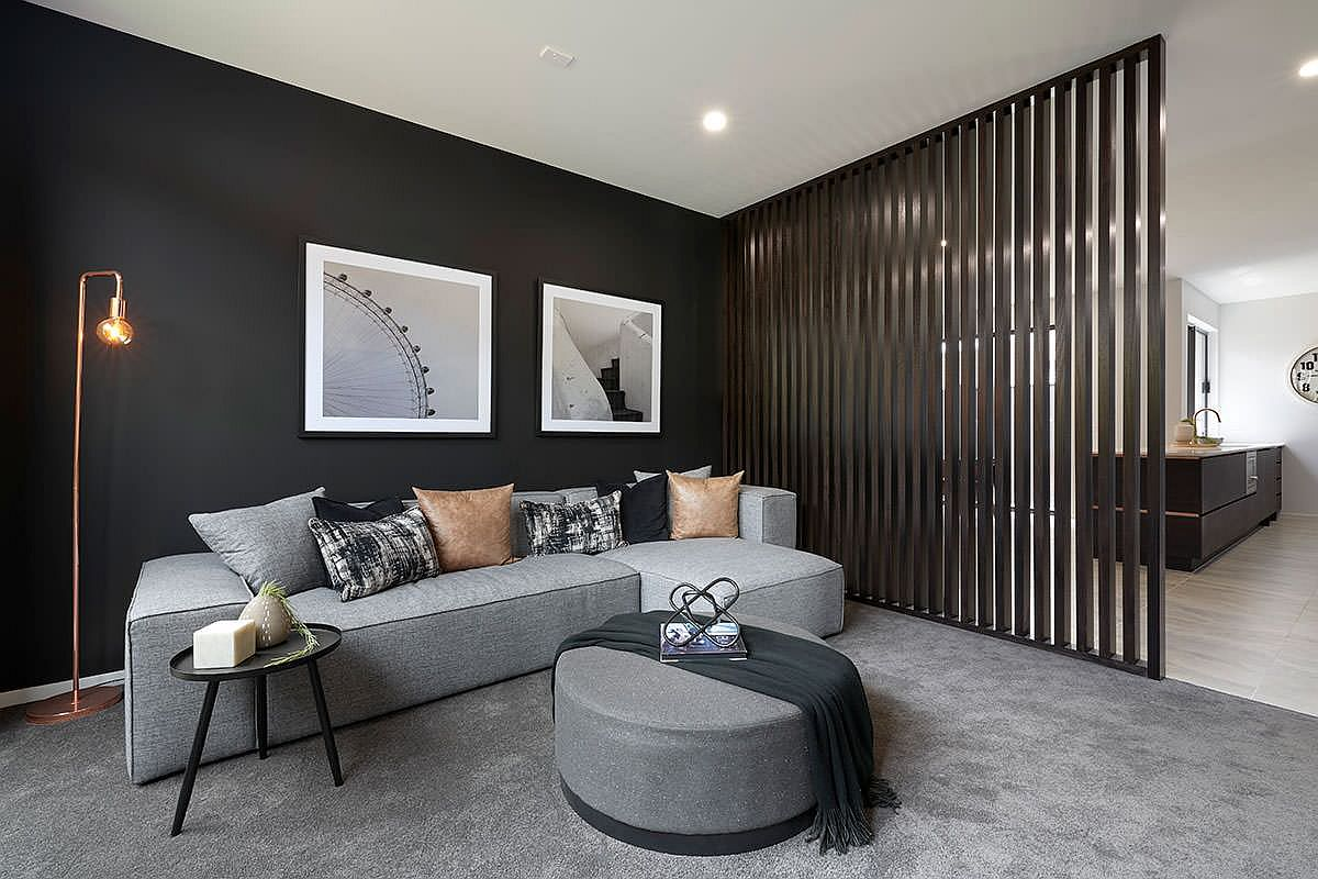 Black wall makes for a lovely backdrop in the spacious, modern living room with gray floor and decor