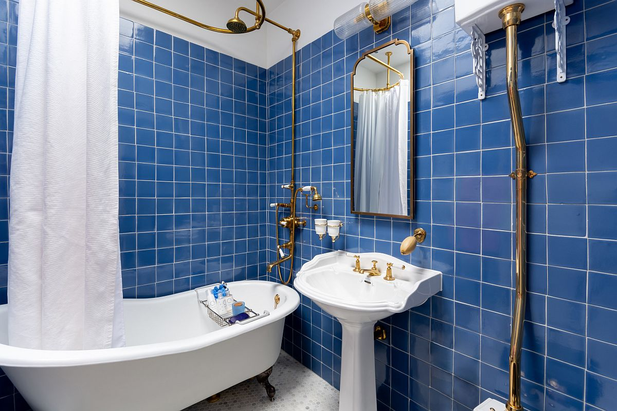 Brass accents add metallic sparkle to the slightly eclectic bathroom in blue and white