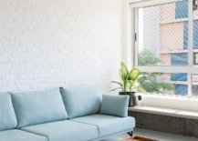 Brick-wall-section-of-the-apartment-provides-backdrop-to-the-beautiful-blue-sofa-in-this-Sao-Paulo-apartment-36180-217x155
