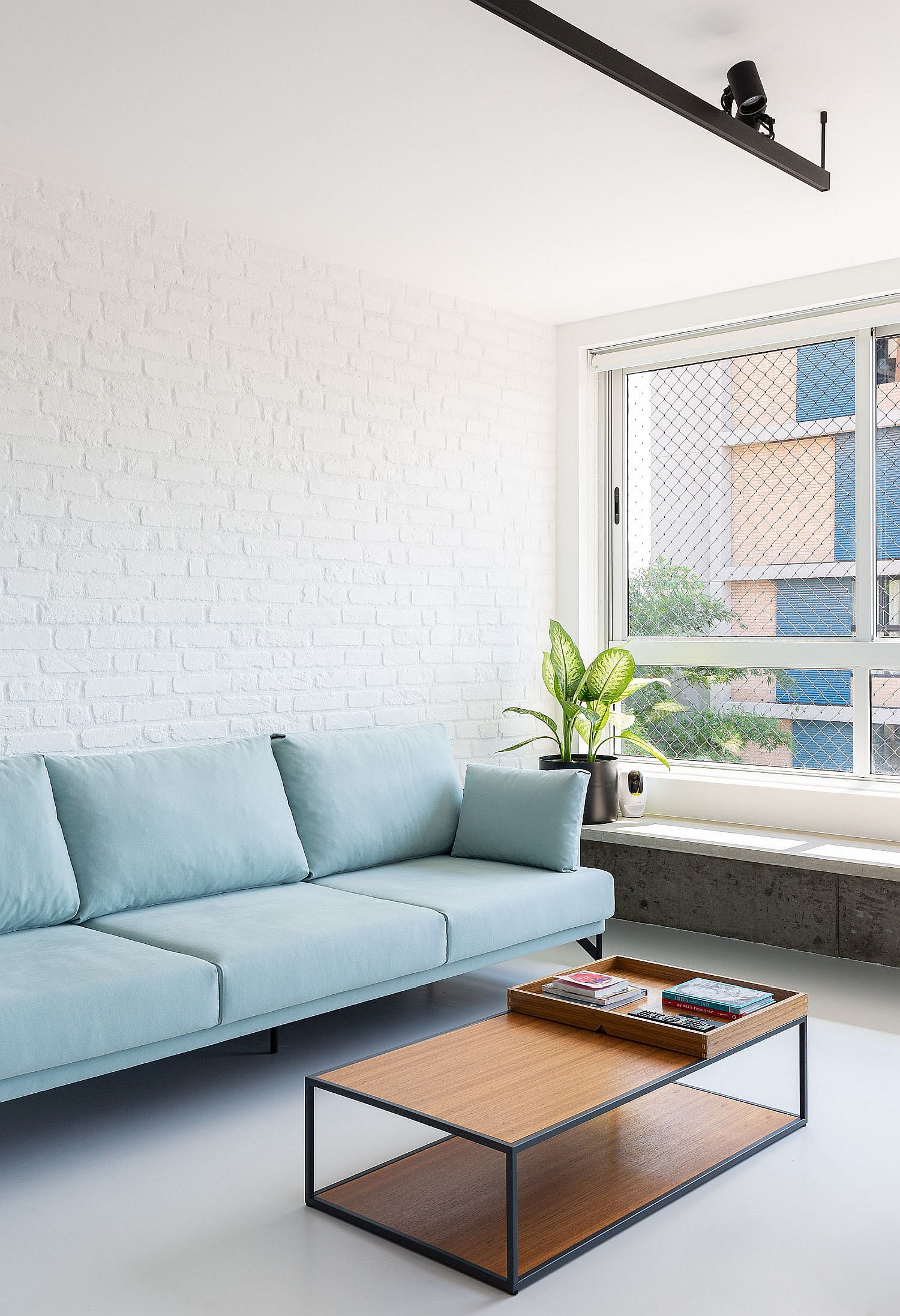 Brick wall section of the apartment provides backdrop to the beautiful blue sofa in this Sao Paulo apartment