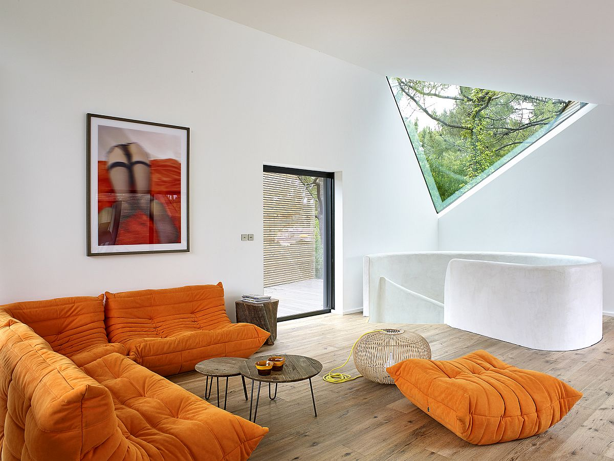 Bright Togo Sofa in orange adds color to the neutral space in white and wood