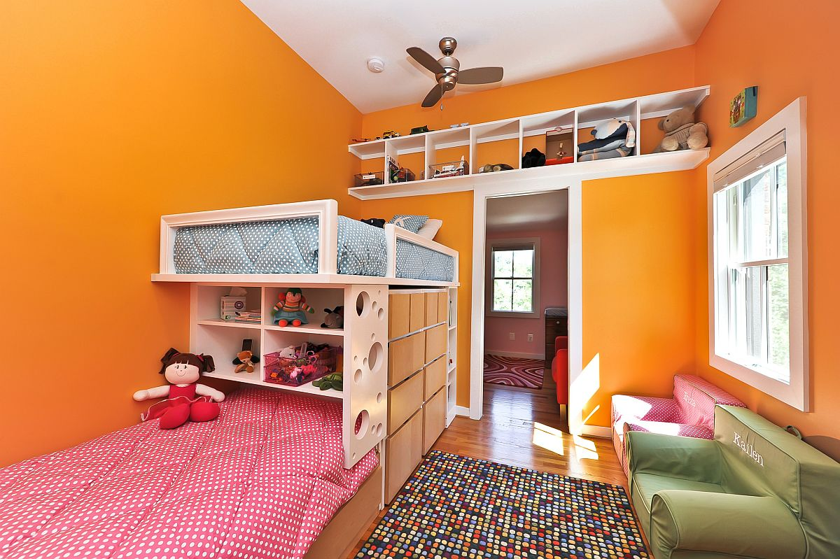 Bright orange walls brighten this girls' room with bunk beds and space-saving design