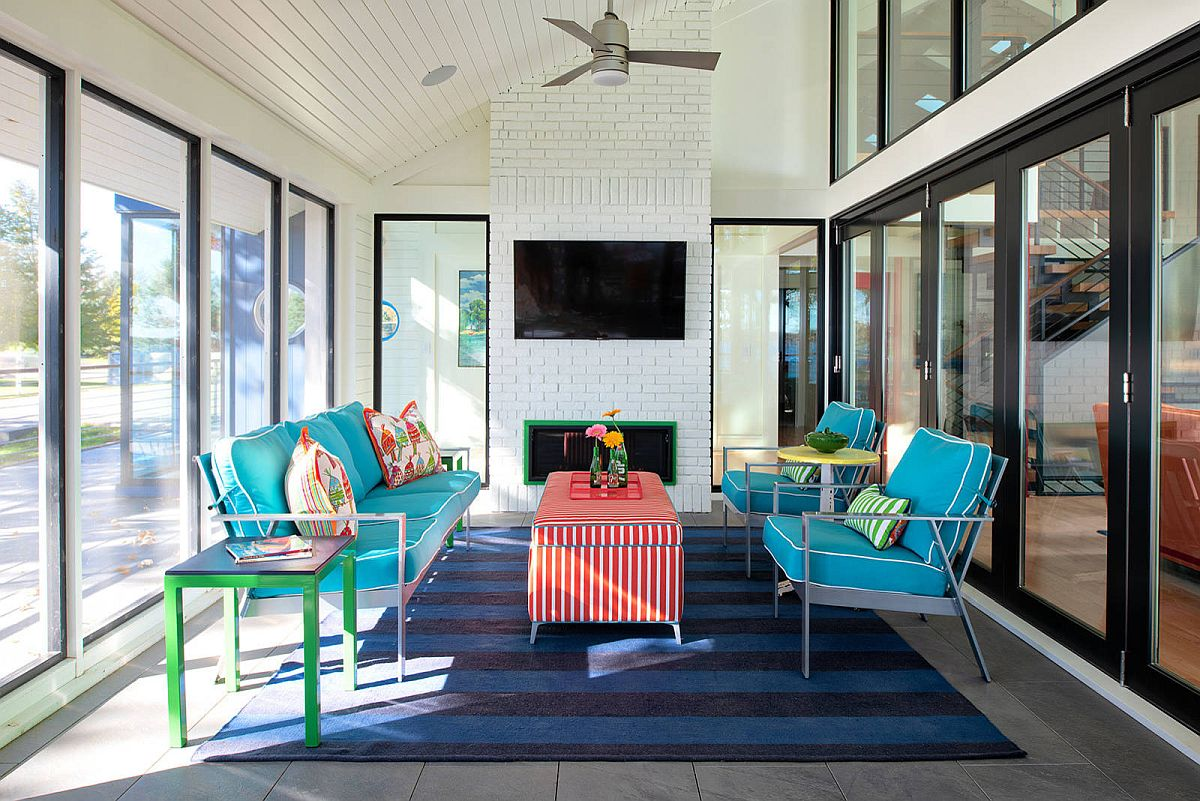 Colorful sofa in blue along with striped chair adds eclectic beauty to the neutral backdrop in this sunroom