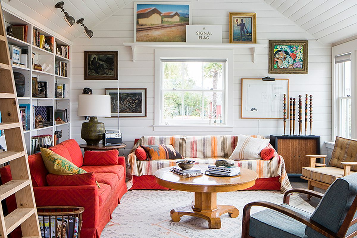 Combining colorful couches and lovely pattern with curated artwork inside living room of coastal home
