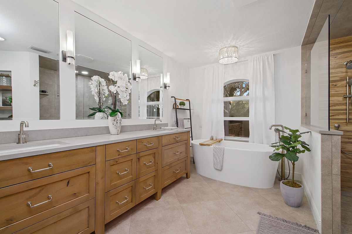 Contemporary bathroom in white with wooden vanity and standalone bathtub at the end