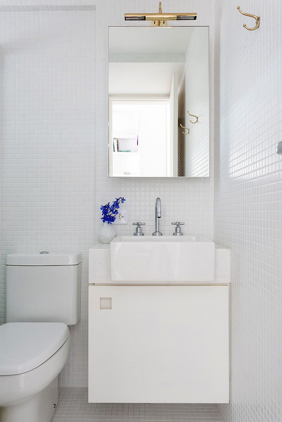 Corner vanity for the small, monochromatic bathroom in white with ample natural light