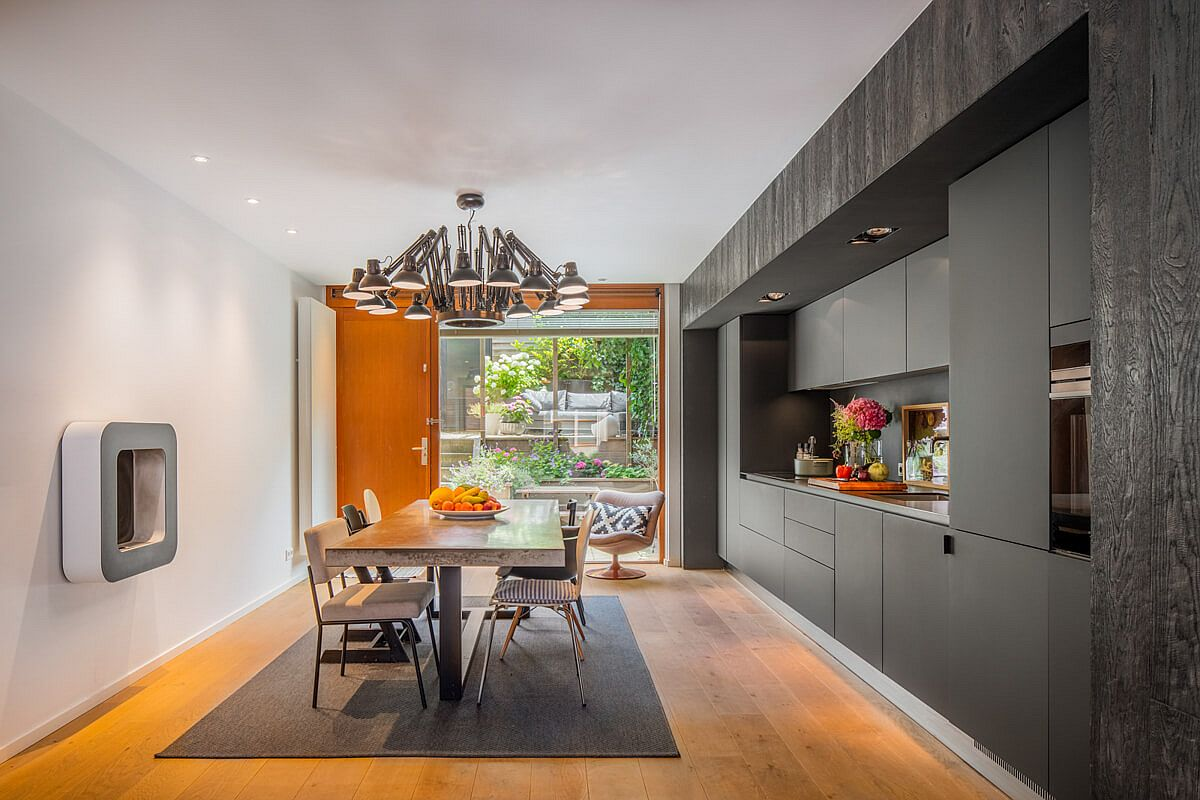 Creating a kitchen and dining area with white walls, gray cabinet and wooden floor that adds visual warmth