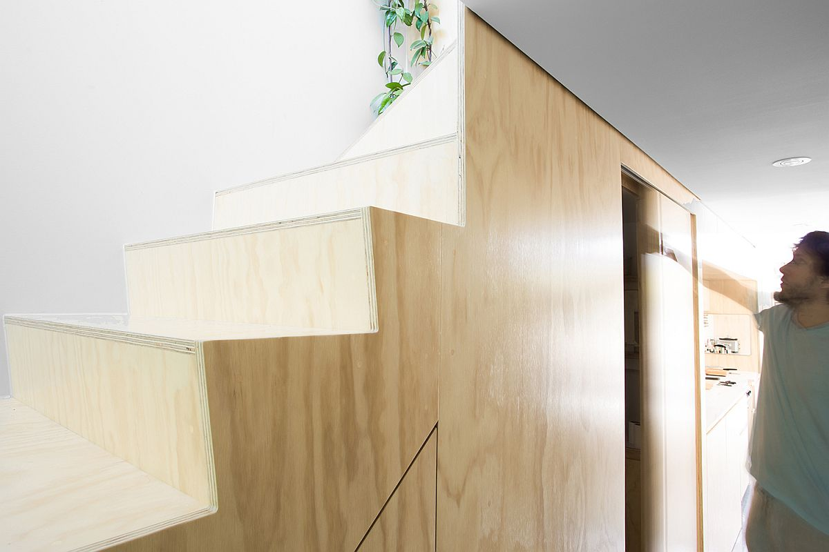 Custom storage space under the plywood staircase maximizes total square footage of the apartment